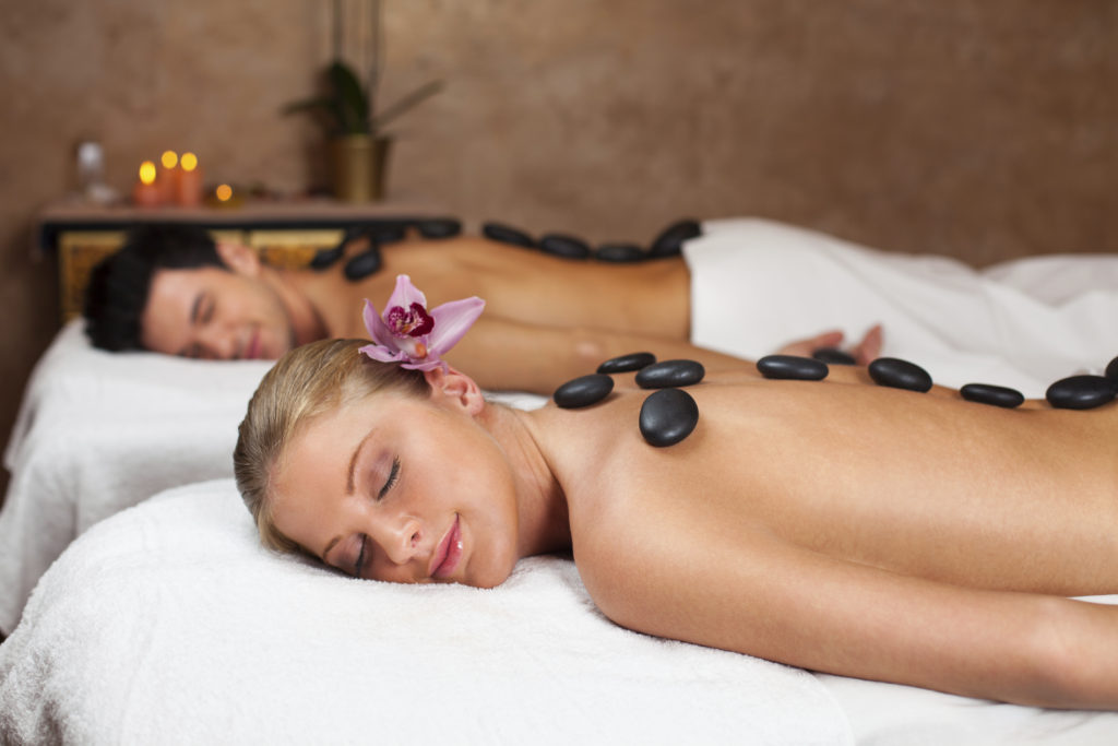 Young couple having a lastone massage in health spa center. Man and woman lying on their stomach on massage table with a Lastone arrangement on their back.